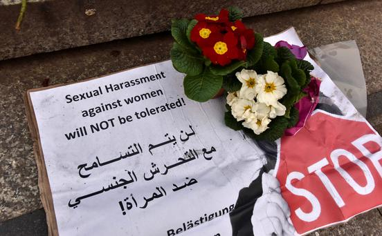 Anger: A banner with flowers placed on the steps to the Cologne Cathedral this week in English and Arabic.