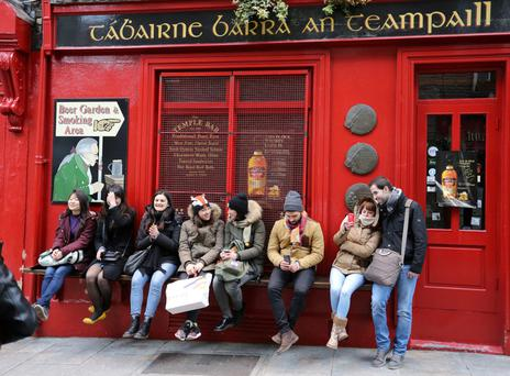 Tourists outside a pub in Temple Bar on Good Friday last year. Irish vintners are campaigning to have the holy day turned into a normal trading day.