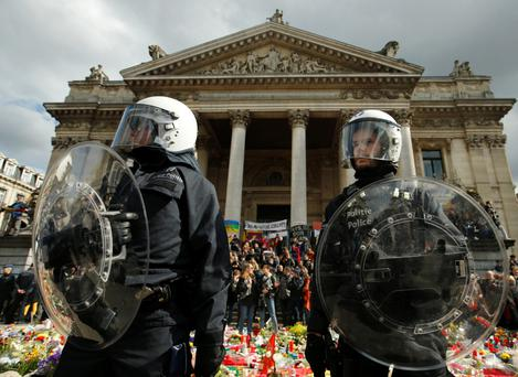 Aftermath: Police in riot gear protect one of the memorials to the victims of the recent Brussels attacks, as right-wing demonstrators protest near the Place de la Bourse in Brussels last week. Photo: AP