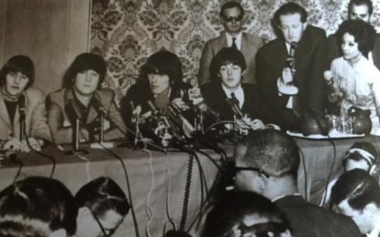 Ringmaster: Tony Barrow (holding microphone) with Brian Epstein (back, in sunglasses) and the Beatles. Photo: Tony Barrow Collection