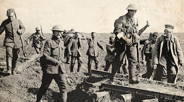 German prisoners help to carry British wounded back to their trenches after an attack by 16th (Irish) Corps on Bavarian units holding Ginchy in September 1916 during the Battle of the Somme. Photo: PA