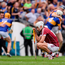 Galway's Jason Flynn tries to come to terms with a devastating defeat while Tipperary's players celebrate a sweet All-Ireland semi-final victory Photo: Piaras Ó Mídheach