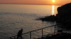 A swimmer at sunrise at the Forty Foot in Sandycove, Dublin
