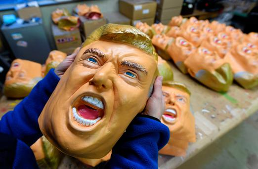 An employee displaying a rubber mask of US President-elect Donald Trump at the Ogawa Studios mask factory in Saitama, north of Tokyo Picture: AFP