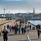 WALKING ON DUN LAOGHAIRE PIER: There has been a sharp drop in belt tightening in the last five years — and it has been driven by younger people and by Dubliners