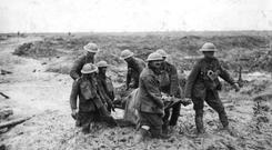 Soldiers carry a wounded comrade during the Battle of Passchendaele in 1917. Photo: John Warwick Brooke/Getty