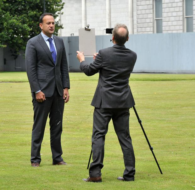 The Taoiseach and his press adviser Nick Miller on the lawn of Government Buildings filming his weekly video message. Photo John Dardis