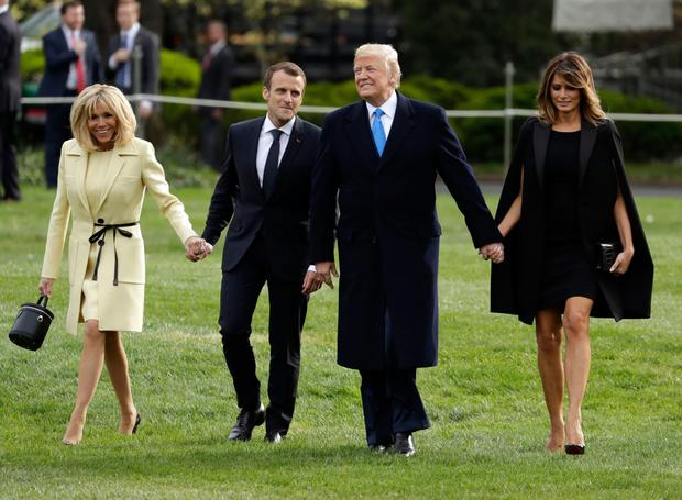 HIGH HEELS ON THE SOUTH LAWN: Donald and Melania Trump walk the rough road with Emmanuel Macron and his wife Brigitte. Photo: AP