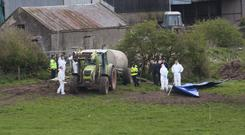A Garda forensic team at the site where Bobby Ryan's body was found in a run-off tank on Mary Lowry's farm