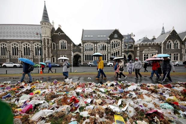 People walk past flowers and tributes displayed in memory of the mosque massacre victims outside the Botanical Gardens in Christchurch
