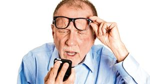 Elderly man struggling to read his phone. Stock picture
