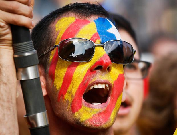 A man painted with the Catalan separatist flag, takes part in a Catalan pro-independence demonstration in Barcelona