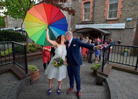 Newly married couple Anne Fox (nee Cole) and Vincent Fox celebrate their wedding day by showing their support for the Yes campaign in favour of same-sex marriage before casting their votes at a polling station on May 22, 2015 in Dublin