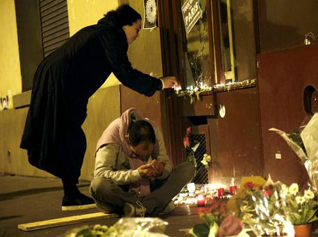 People light candles and pray outside Le Carillon restaurant, one of the sites where 130 people were killed in Paris