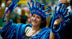 A woman sells 'Happy New Year 2017' headwear on a shopping street in Sydney yesterday. Photo: AFP/Getty Images