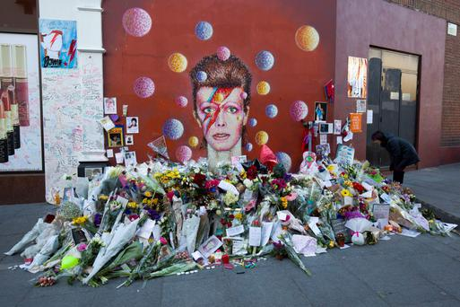 Tributes in front of a mural of Bowie in London last year, painted by Australian street artist James Cochran. Photo: Getty