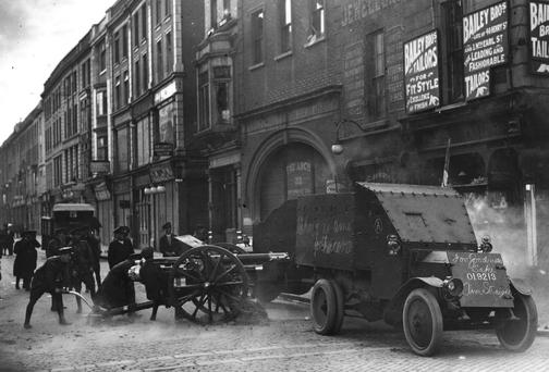 CIVIL STRIFE: Uniformed Free State troops fire an 18-pounder field gun from the top of Henry Street, Dublin at Republican targets in the Gresham Hotel, during the Irish Civil War. A Lancia armoured car is in the foreground. (Photo by Hulton Archive/Getty Images)