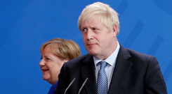 NOTES FROM A SMALL ISLAND: British Prime Minister Boris Johnson holds his notes as he attends a news conference with German Chancellor Angela Merkel in Berlin last Wednesday. Photo: Fabrizio Bensch/Reuters