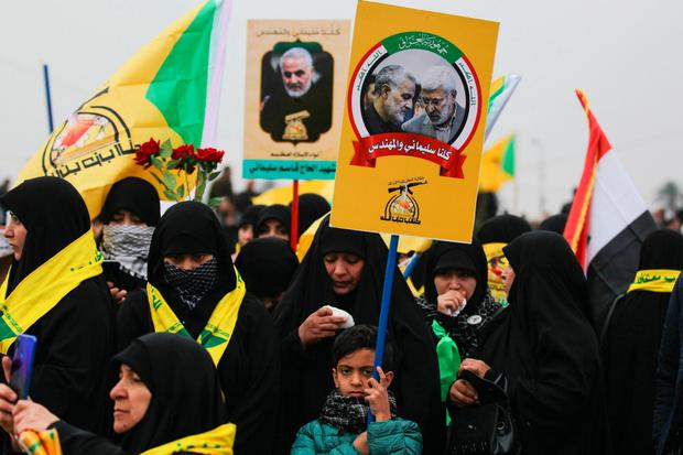 UNITED IN GRIEF: Supporters of the Hashd al-Shaabi militias and Iraq's Hezbollah brigades attend the funeral of Iranian general Qasem Soleimani (portrait) and Iraqi paramilitary chief Abu Mahdi al-Muhandis in Baghdad
