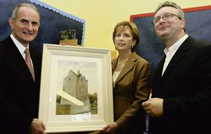 PICTURE THIS: Mary McAleese and her husband Martin, pictured with a painting of Annaghdown Castle, which was presented to the then President during her visit to St. Brendan's National School, Annaghdown. Sean Faughnan, right, is the owner of Annaghdown Castle. Photograph: Iain McDonald