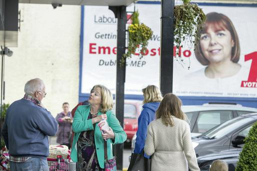 Nessa Childers on the campaign trail in Kimmage as a poster for Emer Costello looms across the road