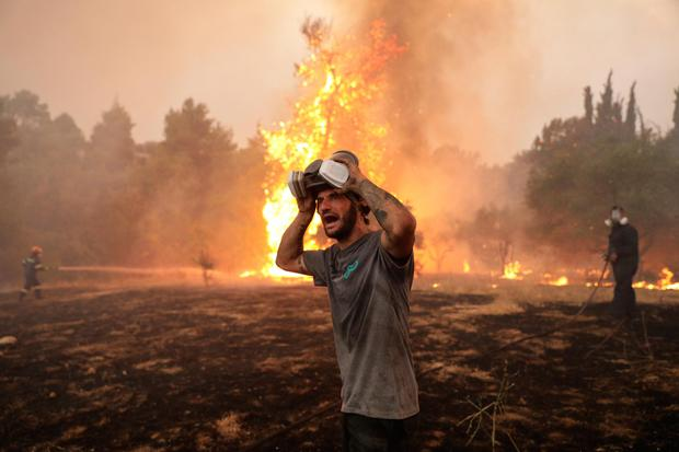 A volunteer battles wildfire in the Greek region of Taxiarches, north of Athens. Picture by Konstantinos Tsakalidis