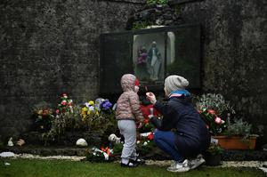 Denise Gormley and her daughter Rosa (7) at the site of the former mother and baby home in Tuam, Co Galway, where the bodies of 796 babies were uncovered. Photo: REUTERS/Clodagh Kilcoyne