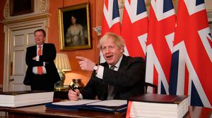 Deal: UK chief trade negotiator David Frost looks on as Prime Minister Boris Johnson signs the EU-UK Trade and Cooperation Agreement in London yesterday. Photo: PA
