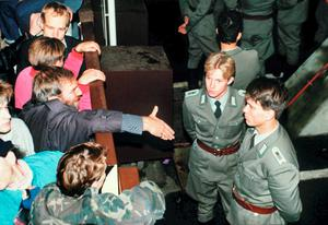 East German border policemen, right, refusing to shake hands with a Berliner who stretches out his hand over the border fence at the eastern site nearby Checkpoint Charlie border crossing point in 1989