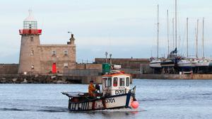 A fishing vessel comes into the harbour in the fishing village of Howth, Dublin. Photo: Brian Lawless/PA Wire