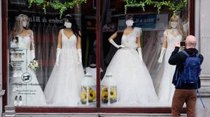 Masked up: A man takes a picture of the window display at a Dublin bridal boutique. Photo: Brian Lawless/PA