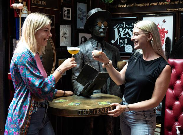 Good health: Yvonne Meppelink (left) and Sacha Wassenaar, visiting from the Netherlands, enjoy a drink in the Temple Bar, Dublin, yesterday as indoor dining in pubs and restaurants reopened across Ireland. Photo: Damien Eagers/PA