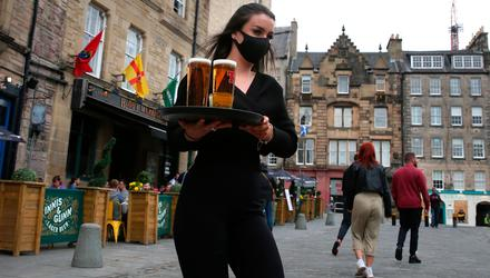 A server carries a tray of drinks from a pub in the Grassmarket in Edinburgh, as beer gardens in Scotland reopened this week. Photo: Andrew Milligan/PA Wire