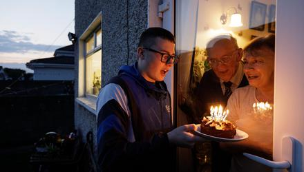 John Power blowing out his birthday cake candles while his grandparents Conor and Ruth McCarthy were cocooning. Photo: Mark Condren