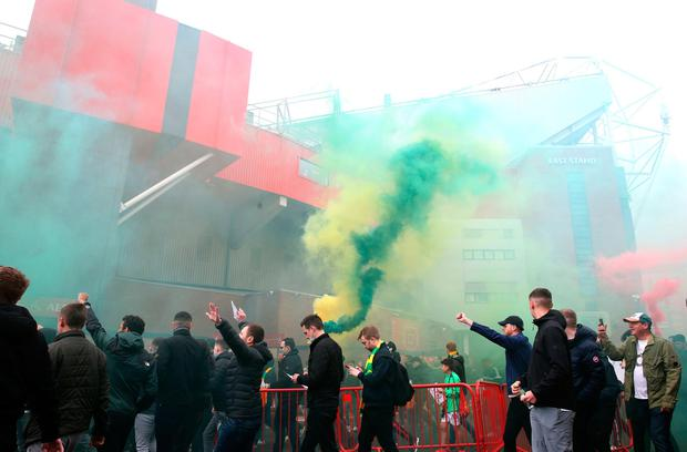 Manchester United fans set off flares before storming Old Trafford last Sunday, in protest against the club's owners. Photo: Barrington Coombs/PA
