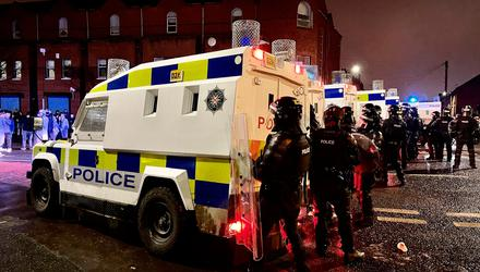 PSNI officers and Land Rovers on the nationalist side of the Springfield Road in Belfast after dispersing people from the area
