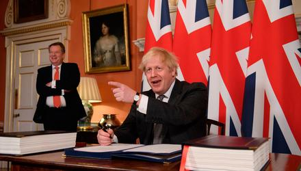 Brexit minister David Frost looks on as UK Prime Minister Boris Johnson signs the EU-UK Trade and Co-operation Agreement last December. Photo: Leon Neal/PA
