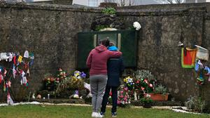 A mother hugs her child after leaving flowers at the shrine at a mass burial site which was formerly part of the Bon Secours Mother and Baby home in Tuam. Photo: Charles McQuillan/Getty