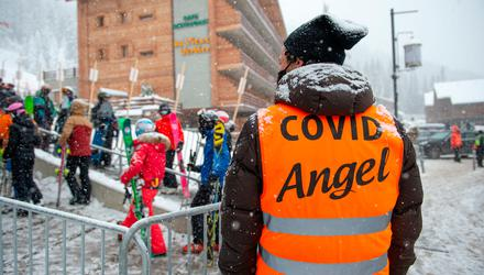 Slippery slope: A steward helps skiers respect Covid safety measures in Verbier, Switzerland, where British tourists fled quarantine.. Photo: Robert Hradil/Getty Images