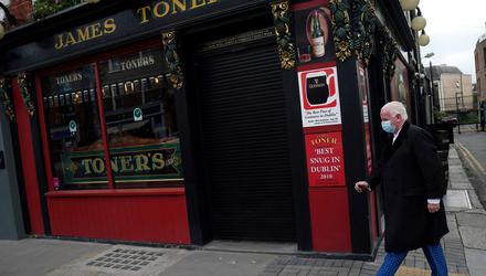 A man wearing a protective face mask walks past a shuttered Toner's pub on Baggot Street, Dublin. Photo: Clodagh Kilcoyne/Reuters