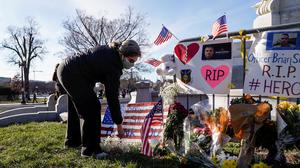Horror: A woman stops at a memorial for Capitol police officer Brian Sicknick who died after he was beaten by supporters of President Donald Trump when they stormed the US Capitol in Washington. Photo: Joshua Roberts/Reuters