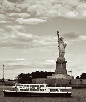 A tourist cruise passes by the Statue of Liberty in New York City