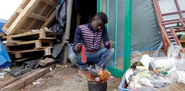 HAVING REACHED THE CONTINENT OF PROMISE: Makbell, of Eritrea, sitting last month by the fire which he uses for cooking and for warmth at a makeshift camp for migrants and asylum seekers in Calais, northern France