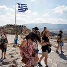 Tourists visit the ancient Acropolis hill in Athens as Greek voters prepare to decide in a referendum on Sunday on whether their government should accept an economic reform package. Photo: Milos Bicanski/Getty Images