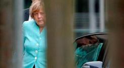 German Chancellor Angela Merkel arriving at the Chancellery in Berlin, Germany, yesterday as France and Germany called for an emergency summit of eurozone leaders to discuss Greece