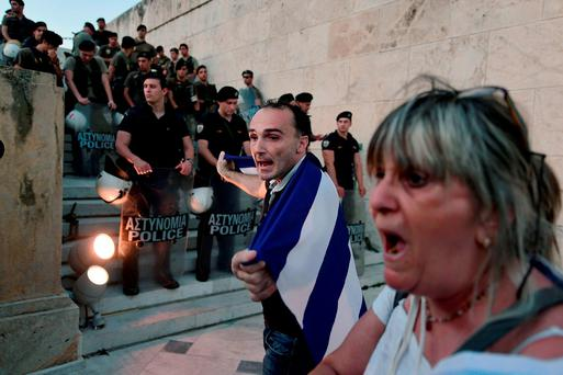 People demonstrate in front of the stairs leading to the Greek parliament in Athens during an anti-EU demonstration in Athens calling for a 'NO' to any agreement with the creditors on July 13, 2015. Eurozone leaders struck a deal Monday on a bailout to prevent debt-stricken Greece from crashing out of the euro, forcing Athens to push through draconian reforms in a matter of days. AFP PHOTO / ANDREAS SOLAROLOUISA GOULIAMAKI/AFP/Getty Images