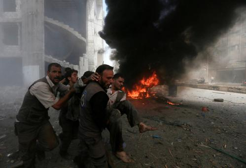 Men transport a casualty after what activists said were air strikes by forces loyal to Syria's President Bashar al-Assad on a market place in the Douma neighborhood of Damascus.