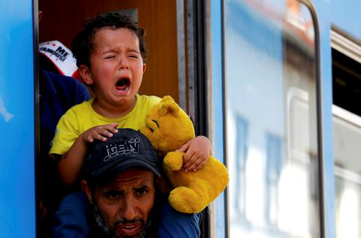A migrant child cries as refugees scramble aboard a train at the station in Beli Manastir, Croatia