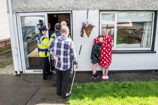 SHOCKING EVICTION: Still in their pyjamas, Fiona Lloyd hugs her distraught 10-year-old son while her blind husband John, still in his bare feet, pleads with gardai and the bailiffs not to evict them from their home in Kells, Co Meath, last week