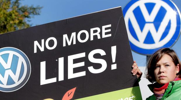 An activist of environmental group Greenpeace holds a protest poster outside the Wolfsburg Volkswagen plant